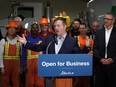 Alberta Premier Jason Kenney (middle) and Alberta Finance Minister Travis Toews (right) announced at Lafarge Infrastructure in Edmonton on Monday May 13, 2019 that their government plans to create jobs in the province by having the lowest corporate business tax rate in Canada.