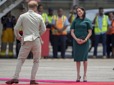 In this Thursday, Oct. 25, 2018 file photo, Prince Harry and Meghan, Duchess of Sussex react before boarding their flight from Nadi, Fiji.