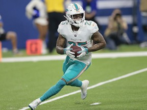 In this Nov. 25, 2018, file photo, Miami Dolphins cornerback Xavien Howard runs back an interception against the Indianapolis Colts during the first half of an NFL football game in Indianapolis. Howard has agreed to terms on a $76.5 million, five-year extension with the Dolphins, the most lucrative deal ever for an NFL cornerback. The contract includes $46 million guaranteed, and ensures Howard will be a cornerstone in the team's rebuilding effort under new coach Brian Flores.