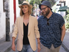 """This image released by Lionsgate shows Charlize Theron, left, and Seth Rogen in a scene from """"Long Shot."""" (Hector Alvarez/Lionsgate via AP)"""