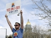 """Chris Olson holds a sign near a busy intersection in downtown Denver on Monday, May 6, 2019, as he urges voters to decriminalize the use of psilocybin, the psychedelic substance in """"magic mushrooms."""" Voters will decide Tuesday whether Denver will become the first U.S. city to decriminalize the drug. (AP Photo/Thomas Peipert)"""