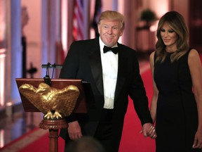 U.S. President Donald Trump with first lady Melania Trump smiles at the invited guests during a White House Historical Association Dinner in the East Room of the White House, Wednesday, May 15, 2019, in Washington.