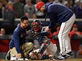 Trainer Masa Abe and manager Rocco Baldelli #5 of the Minnesota Twins check on Mitch Garver #18 after a collision at home plate with Shohei Ohtani #17 of the Los Angeles Angels of Anaheim during the eighth inning of the game on May 14, 2019 at Target Field in Minneapolis, Minnesota.