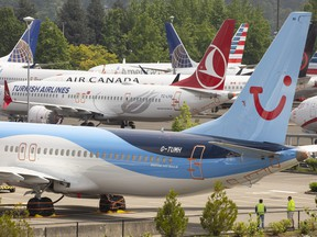 Workers stand near Boeing 737 MAX airplanes as they sit parked at a Boeing facility adjacent to King County International Airport, known as Boeing Field, on May 31, 2019 in Seattle, Wash.