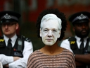 A demonstrator wearing a mask depicting Julian Assange protests as police officers stand guard outside of Westminster Magistrates Court, where a case hearing for U.S. extradition of Wikileaks founder Julian Assange is held, in London, June 14, 2019. REUTERS/Hannah Mckay