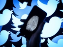 In this photo illustration, a thumbprint is displayed on a mobile phone as the logo for the Twitter social media network is projected onto a screen on August 09, 2017 in London, England.