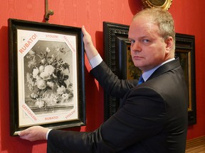 """A file handout picture realeased by the Florence Museum Press Office on January 1, 2019 shows the Florence Uffizi Galleries director Eike Schmidt with a copy of the """"Vase of Flowers"""" by Dutch painter Jan van Huysum, stolen from the Wehrmacht's Pitti Palace during World War II, in Florence. - The German Foreign Ministry announced on June 29, 2019 that it will return to the Palazzo Pitti in Florence a painting by a Dutch painter stolen by the Nazis during the Second World War. (FLORENCE MUSEUM PRESS OFFICE / Getty Images)"""