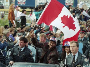 Toronto Blue Jays' Joe Carter waves the Canadian flag alongside his wife Diana during a World Series victory parade in Toronto on Sunday, October 24, 1993. The Raptors' historic NBA championship win last week marked the first time a Canadian team has won one of the big four professional sports championships since the Toronto Blue Jays won the 1993 World Series.