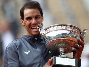 Rafael Nadal of Spain bites the trophy after defeating Dominic Thiem of Austria in the final during Day Fifteen of the 2019 French Open at Roland Garros on June 9, 2019 in Paris. (Julian Finney/Getty Images)