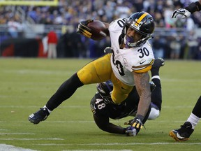 Running Back James Conner of the Pittsburgh Steelers is tackled by inside linebacker Patrick Onwuasor of the Baltimore Ravens in the fourth quarter at M&T Bank Stadium on November 4, 2018 in Baltimore, Maryland.