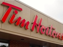 In this file photo taken on Aug. 27, 2014 the sign over a Tim Hortons coffee-and-donut shop is viewed in Magog, Quebec.