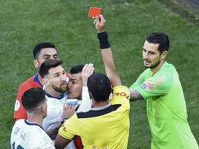 Paraguayan referee Mario Diaz de Vivar shows the red card to Argentina's Lionel Messi and Chile's Gary Medel as they have a physical encounter during the Copa America football tournament third-place match at the Corinthians Arena in Sao Paulo, Brazil, on July 6, 2019. (EVARISTO SA/AFP/Getty Images)