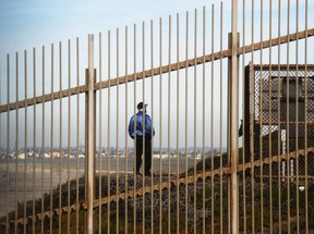 A beach visitor stands on the U.S. side of the barrier on the U.S.-Mexico border, next to the Pacific Ocean, on Jan. 8, 2019 as seen from Tijuana, Mexico.