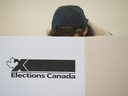 A woman marks her ballot behind a privacy barrier in the riding of Vaudreuil-Soulanges, west of Montreal, on October 19, 2015. A Federal Court judge is ordering the chief electoral officer to take a second look at whether voting day this October needs to be moved because it falls on a Jewish holiday.