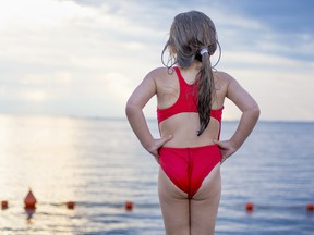 A little Caucasian girl on the platform before jumping into the sea