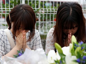 Women pray in front of bouquets placed for victims of the torched Kyoto Animation building in Kyoto, Japan, July 20, 2019. (REUTERS/Kim Kyung-Hoon)