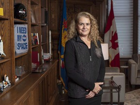 Gov. Gen. Julie Payette stands next to a shelf featuring memorabilia from her career as an astronaut, in her office at Rideau Hall in Ottawa on Dece. 11, 2018.