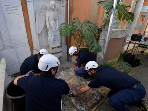 People open tombs in a cemetery on the Vatican's grounds to test the DNA of bones to help solve the 36-year-old disappearance of a teenage daughter of a clerk in the Holy See, in the Vatican July 11, 2019. (Vatican Media/Handout via REUTERS)