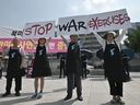 Anti-war activists hold placards reading