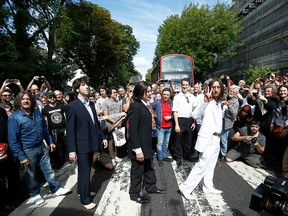 People take pictures as the Beatles cover band members walk on the zebra crossing on Abbey Rod. in London, England, Aug. 8, 2019.