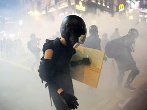 Demonstrators are seen amidst smoke from tear gas during an anti-extradition bill protest in Hong Kong on Sunday, Aug. 4, 2019.