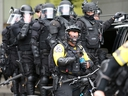 A cop removes his helmet to take a sip of water as alt-right groups march down the street during the End Domestic Terrorism rally on August 17, 2019 in Portland, Oregon. (Karen Ducey/Getty Images)