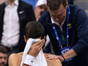 Novak Djokovic of Serbia has his shoulder worked on by a trainer while playing Stan Wawrinka of Switzerland during their Round Four Men's Singles match at the 2019 US Open at the USTA Billie Jean King National Tennis Center in New York on September 1, 2019. (Don Emmert / Getty Images)
