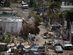 A man carrying a water container walks next to damaged houses after the area was hit by Hurricane Maria in Canovanas, Puerto Rico, September 26, 2017.