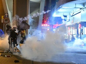 A protester throws back a tear gas canister fired by police in Sham Shui Po as a pro-democracy march was held in the Kowloon district in Hong Kong on October 20, 2019.
