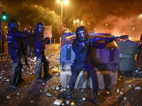 Armed police officers stand in front of protesters as objects are thrown during a protest over the jail sentences given to separatist politicians by Spains Supreme Court, on October 18, 2019 in Barcelona, Spain. (Jeff J Mitchell/Getty Images)