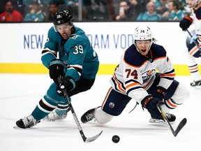 Logan Couture #39 of the San Jose Sharks and Ethan Bear #74 of the Edmonton Oilers go for the puck at SAP Center on November 12, 2019 in San Jose, California.