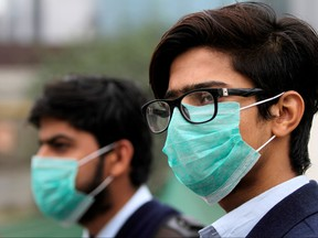 Men wearing protective masks wait for a bus in Lahore, Pakistan Nov. 22, 2019. REUTERS/Mohsin Raza