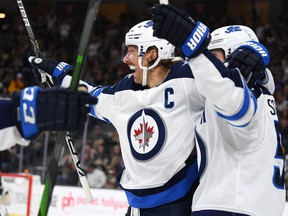 Winnipeg Jets center Mark Scheifele (55) celebrates with captain Blake Wheeler after scoring a goal in the third period against the Vegas Golden Knights to tie the game at T-Mobile Arena in Las Vegas on Saturday.