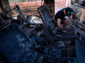 A member of the LeBaron family looks at the burned car where part of the nine murdered members of the family were killed and burned during an ambush in Bavispe, Sonora mountains, Mexico, on Nov.  5, 2019.