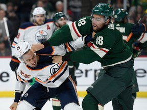 ST PAUL, MINNESOTA - DECEMBER 12: Darnell Nurse #25 of the Edmonton Oilers and Jordan Greenway #18 of the Minnesota Wild throw punches during the second period of the game at Xcel Energy Center on December 12, 2019 in St Paul, Minnesota.