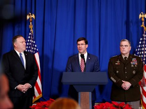 U.S. Defense Secretary Mark Esper, centre, speaks about airstrikes by the U.S. military in Iraq and Syria, at the Mar-a-Lago resort in Palm Beach, Fla., Dec. 29, 2019. With him are U.S. Army General Mark Milley,  right, and U.S. Secretary of State Mike Pompeo. (REUTERS/Tom Brenner)