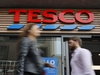 (FILES) In this file photo taken on September 30, 2019 people walk past at a Tesco Express in central London. - Supermarket giant Tesco has stopped production at a factory in China after one of its Christmas cards was found to contain a cry for help from a prisoner who made it, the store said on Sunday, December 22. (Photo by Tolga AKMEN / AFP) (Photo by TOLGA AKMEN/AFP via Getty Images)