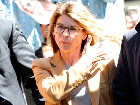 Lori Loughlin (C) arrives at the court to appear before Judge M. Page Kelley to face charges for allegedly conspiring to commit mail fraud and other charges in the college admissions scandal at the John Joseph Moakley United States Courthouse in Boston on April 3, 2019.