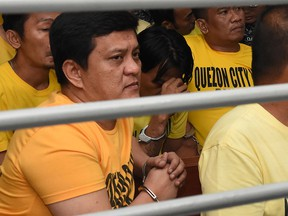 This handout photo from the Supreme Court - Public Information Office (SC-PIO)  taken and released on Dec. 19, 2019 shows Andal Ampatuan Jr. (L) and others accused of involvement in the 2009 Maguindanao massacre waiting to hear the court's verdict at the trial venue inside a prison facility in Manila.