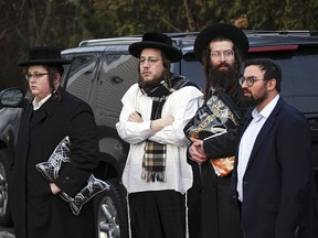 Members of the Jewish community gather outside the home of rabbi Chaim Rottenbergin Monsey, in New York on December 29. (KENA BETANCUR/AFP via Getty Images)