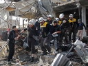 Members of the Syrian Civil Defence (White Helmets) recover a victim following a regime air strike on December 2, 2019 in a market in the town of Maaret al-Numan. (ABDULAZIZ KETAZ/AFP via Getty Images)