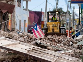 In this file photo taken on January 8, 2020, A Puerto Rican flag waves on top of a pile of rubble as debris is removed from a main road in Guanica, Puerto Rico, after the January 7 earthquake. - A 6.0 magnitude earthquake rocked Puerto Rico on January 11, 2020, the latest in a series of powerful tremors that have struck the US territory in recent days, the US Geological Survey reported. The latest quake was felt at 8:54 am local time (1254 GMT) 14 kilometers (eight miles) southeast of Guanica, a town on the island's southern Caribbean coastline that was hard hit by earlier quakes.