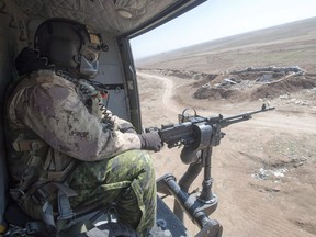 A Canadian Forces door gunner keeps watch as his Griffon helicopter goes on a mission, Feb. 20, 2017 in northern Iraq.