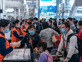 Travellers wearing face mask wait in line at the departure hall of West Kowloon Station on Jan. 23, 2020 in Hong Kong.
