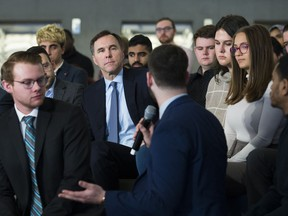 Canadian federal Finance Minister Bill Morneau, back centre, listens to a question from a Ryerson University student as he launches consultations for the Budget 2020 at a town hall discussion in Toronto on Monday, January 13, 2020.