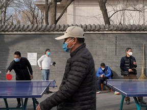 People wearing face masks play table tennis at a park, following an outbreak of the novel coronavirus in the country, in Beijing, Feb. 21, 2020. REUTERS/Stringer