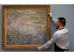 In this file picture taken on June 18, 2014, a Sotheby's employee poses with a painting by late French impressionist painter Claude Monet, entitled 'Nympheas' which was sold at an auction in London on Monday, June 23, 2014.