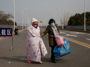A leukemia patient and her mother coming from Hubei province cross a checkpoint at the Jiujiang Yangtze River Bridge in Jiujiang, Jiangxi province, China, as the country is hit by an outbreak of a new coronavirus, February 1, 2020. (REUTERS/Thomas Peter)