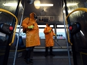 Men wearing protective gear spray disinfectant as part of preventive measures against the spread of the COVID-19 coronavirus, inside a bus at a terminal in Tbilisi on March 2, 2020. (VANO SHLAMOV/AFP via Getty Images)