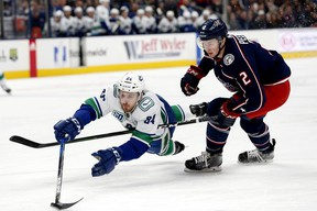 Vancouver Canucks centre Brandon Sutter reaches for the puck ahead of Columbus Blue Jackets defenseman Markus Nutivaara in the first period at Nationwide Arena.